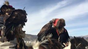Kasachisches Adlerjäger berkutchi mit dem Pferd, das zu den Hasen mit Steinadler in den Bergen von Bayan-Olgiiaimag jagt stock video