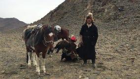 Kasachisches Adlerjäger berkutchi mit dem Pferd, das zu den Hasen mit Steinadler in den Bergen von Bayan-Olgiiaimag jagt stock video footage