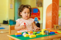 Kasachisches gelocktes Mädchen, das in Kinderentwicklungszentrum spielt Stockfoto