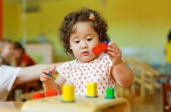 Kasachisches gelocktes Mädchen, das in Kinderentwicklungszentrum spielt Lizenzfreie Stockbilder