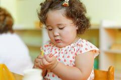 Kasachisches gelocktes Mädchen, das in Kinderentwicklungszentrum spielt Lizenzfreies Stockfoto