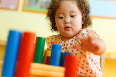 Kasachisches gelocktes Mädchen, das in Kinderentwicklungszentrum spielt Lizenzfreie Stockfotos