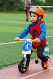 KASAKHSTAN ALMATY - JUNI 11, 2017: Barn` s som cyklar konkurrenser, turnerar de-ungar Barn som åldras 2 till 7 år, konkurrerar in Royaltyfri Bild