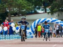 KASAKHSTAN ALMATY - JUNI 11, 2017: Barn` s som cyklar konkurrenser, turnerar de-ungar Barn som åldras 2 till 7 år, konkurrerar in Royaltyfri Fotografi