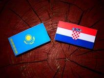 Kasakhstan flagga med den kroatiska flaggan på en trädstubbe Fotografering för Bildbyråer