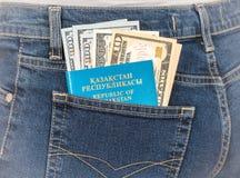 Kasakhstan pass- och dollarräkningar i den tillbaka jeansen stoppa i fickan Royaltyfri Foto