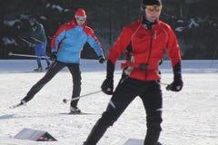 KASAN, RUSSLAND - MÄRZ 2018: Zwei Skifahrer, die auf Skibahn laufen Lizenzfreie Stockbilder