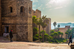 Kasbah of the Udayas. Rabat, Morocco. Rabat, Morocco - December 11, 2015: Youths front of walls of Kasbah of the Udayas. Is a small fortified complex and a Stock Image