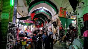 In Kashan Grand Bazaar, Iran. KASHAN, IRAN - OCTOBER 22, 2017: Medieval building of Grand Bazaar with crowded alleyway, full of stores, stalls and visitors, on stock footage