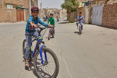 Boy cyclist posing for photographer on city street, Kashan, Iran. Kashan, Iran - April 27, 2017: Boys of school age ride bicycles outdoors in a residential area Stock Images