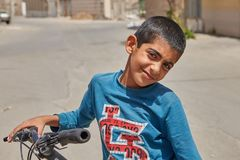 Boy bicyclist posing for photograph on city street, Kashan, Iran. Kashan, Iran - April 27, 2017: A close-up portrait of an unknown Iranian boy, about 12 years Royalty Free Stock Images