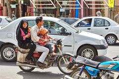 Parents with two daughters ride motorcycle through city, Kashan, Iran. stock images