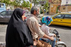 Three people ride a motorcycle on city street, Kashan, Iran. Kashan, Iran - April 27, 2017: A family of three, parents and a little girl, ride on one motorcycle Royalty Free Stock Photos
