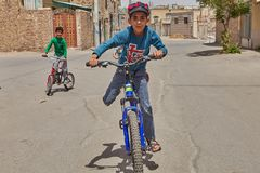 Boy is cycling in yard with friends, Kashan, Iran. Kashan, Iran - April 27, 2017: Friends of teenagers ride bicycles in the area of private low-rise buildings Royalty Free Stock Images