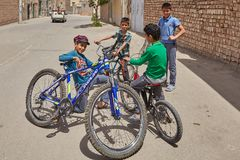 Courtyard team of cyclists met outdoors, Kashan, Iran. Kashan, Iran - April 27, 2017: A group of teenage boys bicyclists playing on the street near their homes royalty free stock images