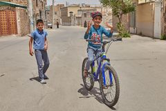 The Iranian boy demonstrates his cycling skills, Kashan, Iran. Kashan, Iran - April 27, 2017: An Iranian boy of middle school age shows that he can ride a Royalty Free Stock Photography