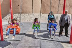 Iranian children swing on swing in park, Kashan, Iran. Kashan, Iran - April 26, 2017: Iranian children swing on a swing, their parents are behind them stock photography