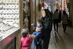 Iranian family near jewelry store on the market, Kashan, Iran. Kashan, Iran - April 25, 2017: Iranian family - a woman with a little boy in her arms and girl Stock Photo