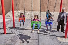 Iranian little children swing on swing, Kashan, Iran. Kashan, Iran - April 26, 2017: Iranian girls and boy are rocking on a swing, a woman in a hijab and a man royalty free stock photos