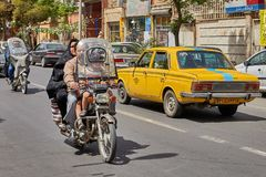 Iranian family on a motorbike on busy street, Kashan, Iran. Kashan, Iran - April 27, 2017: Iranian man, his wife in a hijab and their little son are riding a Stock Photos