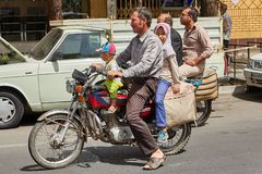 Iranian man with his family on a motorcycle, Kashan, Iran. Kashan, Iran - April 27, 2017: Iranian man is riding with his daughter and son on a motorcycle Royalty Free Stock Photo