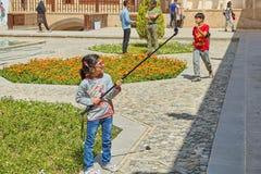 Little Iranian girl in Tabatabaei historical house, Kashan, Iran. Kashan, Iran - April 26, 2017: little Iranian girl is making photos in Tabatabaei historical royalty free stock photos