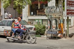 Father and daughter ride motorbike on city street, Kashan, Iran. Kashan, Iran - April 27, 2017: A mature man rides a motorbike on a city street, his passenger Stock Photography