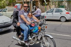 Man is riding a motorcycle with his family, Kashan, Iran. Kashan, Iran - April 27, 2017: A mature man is riding a motorbike with his wife and daughter on a Stock Images