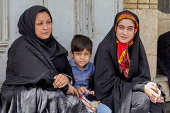 Islamic family, two women and a small boy, Kashan, Iran. Kashan, Iran - April 27, 2017: A Muslim family, two women and one young boy, are waiting for the Royalty Free Stock Photo
