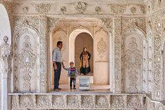 Muslim man with son in Tabatabaei historical house, Kashan, Iran. Kashan, Iran - April 26, 2017: muslim man with his son stand near the altar in Tabatabaei royalty free stock photo