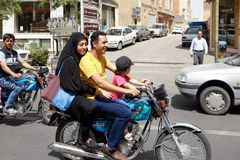 Muslim family on a motorcycle on a busy street, Kashan, Iran. Kashan, Iran - April 27, 2017: Muslim man, his wife in a hijab and their little daughter are stock image