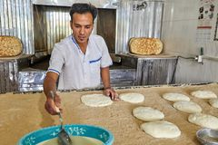 Baker put flattened dough on bakery table, Kashan, Iran. stock photos