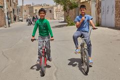 Boys ride on bicycles in low-rise residential area, Kashan, Iran. Kashan, Iran - April 27, 2017: Two teenagers on bicycles play in the open air among low-rise Stock Photo