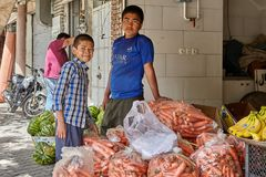 Two boys work in a vegetable shop, Kashan, Iran. Kashan, Iran - April 27, 2017: Two teenagers are standing near sacks with fresh carrots in a vegetable shop Stock Images