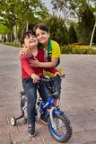Two Iranian boys ride a bicycle, Kashan, Iran. Kashan, Iran - April 25, 2017: two unknown little Iranian boys, about 6 years old, ride a bicycle in the park stock image