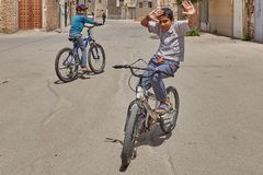 Teenage boy shows tricks on bicycle, Kashan, Iran. Kashan, Iran - April 27, 2017: An unknown boy teenager shows tricks on a bicycle in the area of private low stock image