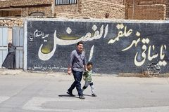 Father and son are walking along the street, Kashan, Iran. Kashan, Iran - April 26, 2017: A young man and a little boy walk along the street past the wall with stock photos