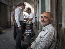 KASHAN, IRAN - AUGUST 13, 2016: Old Iranian egg seller smiling after a closing deal with fellow Iranian people in the background Royalty Free Stock Photo