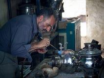 KASHAN IRAN - AUGUSTI 13, 2016: Hantverkare som reparing en samovar i den Kashan basaren, Iran Arkivbild