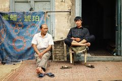 two uyghur man in front of their jewelry store stock image