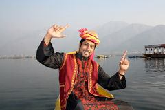 Kashmiri Boy Dancing to a Folk Song on a Shikara. Pathani boy (North Indian) in tradition burqa dress sitting on a shikara boat and dancing to a folk song Royalty Free Stock Images
