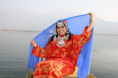 Kashmiri Girl Lifting her Blue Veil. Very attractive Kashmir girl in 20s lifting her blue veil on a Shikara at Dal Lake Stock Photography