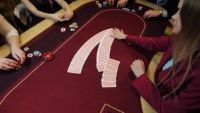 Kasino: återförsäljarekvinnan hasar pokerkorten på tabellen Kasinovågspel långsam rörelse arkivfilmer
