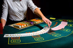 Kasino: Återförsäljaren hasar pokerkorten Royaltyfria Bilder