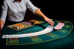 Kasino: Återförsäljaren hasar pokerkorten Royaltyfri Foto