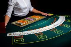 Kasino: Återförsäljaren hasar pokerkorten Royaltyfri Bild
