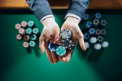 Kasino playes, die eine Handvoll Chips halten Lizenzfreie Stockfotos