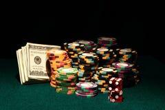 Kasino-Schürhaken-Chips mit Geld und Würfeln Stockfoto