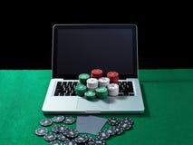 Kasinochiper och kort på tangentbordanteckningsboken på den gröna tabellen Arkivfoton