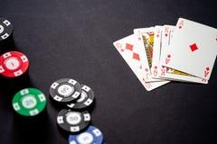 Kasinochiper och spela kort på minimalistic svart bakgrund exponeringskunglig person arkivbild